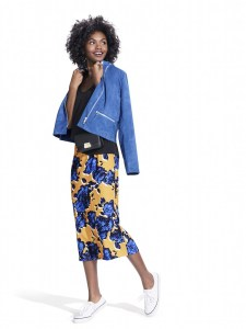 studio-model-wearing-blue-suede-jacket-with-black-tee-black-leather-fanny-pack-blue-black-white-and-yellow-floral-skirt-and-white-sneakers